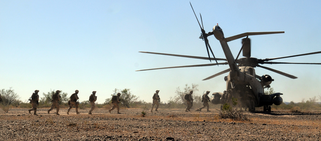 A line of Marines run to a waiting helicopter.